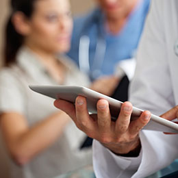 male doctor using digital tablet with colleagues in background