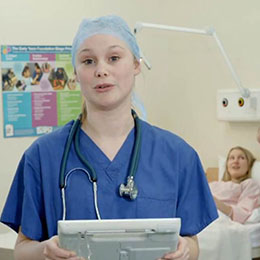 female doctor holding portable computing device